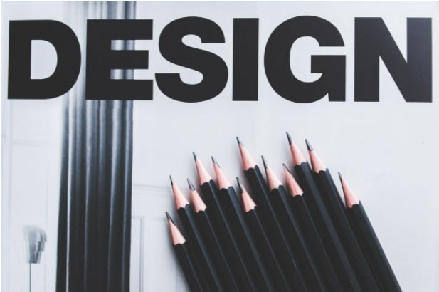 "The word ""design"" in bold letters along with black pencils"